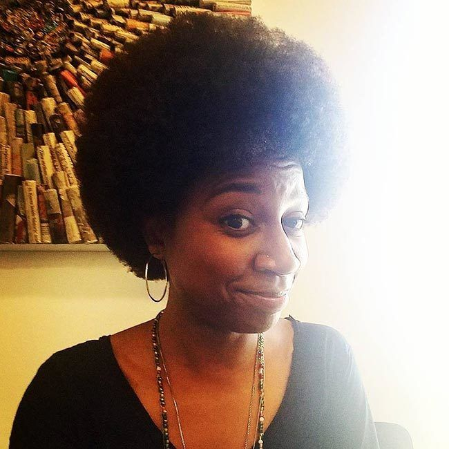 African-American woman with large afro smirks at camera.