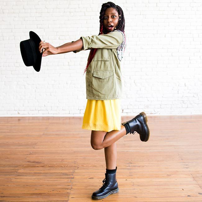 gerilyn hayes wears a yellow dress, sequined military-style jacket, black Dr Marten boots, and a black hat onto of ombre red box braids