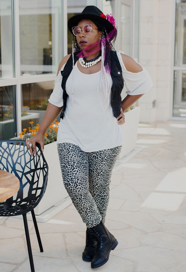 Editor April B in leopard print pants, pink/black braids, and a white cold-shoulder blouse