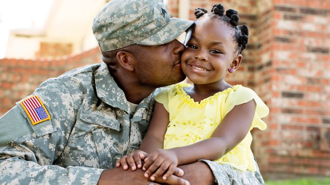 A black father in military dress hugs his daughter who is wearing Bantu knots and a big smile