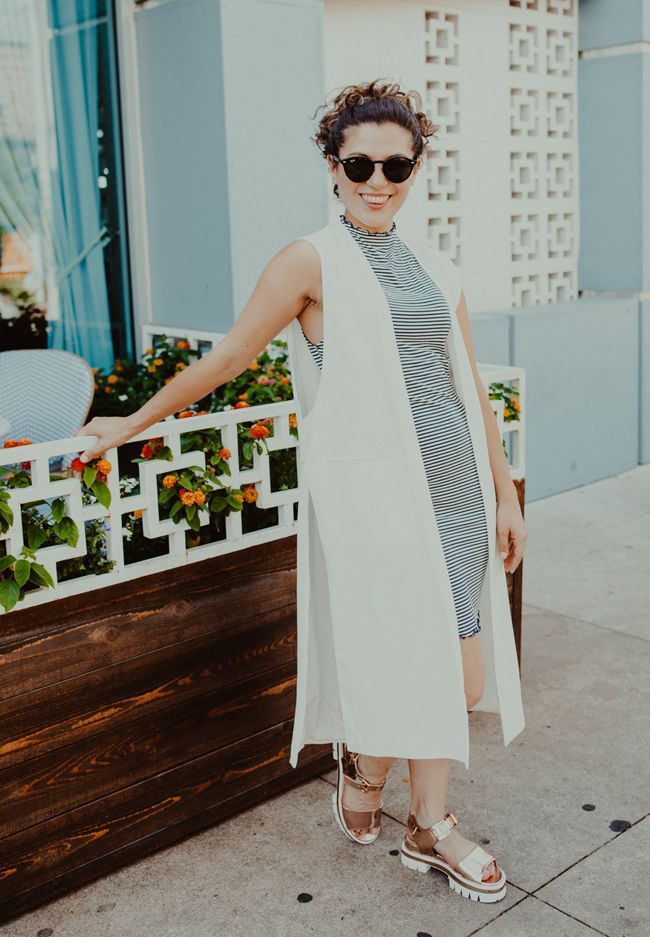girl wearing white duster jacket, striped dress, platform sandals