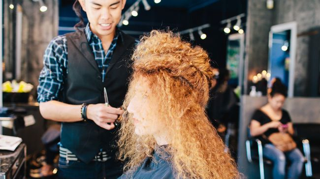 hairstylist cutting curly hair