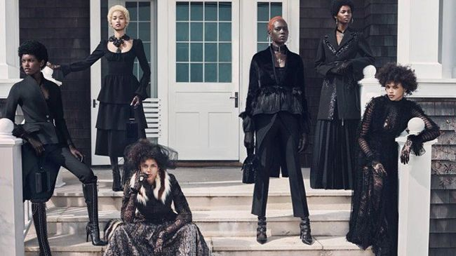Six black women with natural hair and goth styling gather outside some house steps in the sun