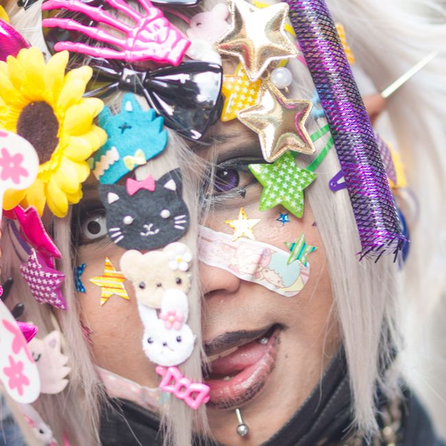 A Japanese woman with most of her bleached white hair covered in cutesy clips licks her lips