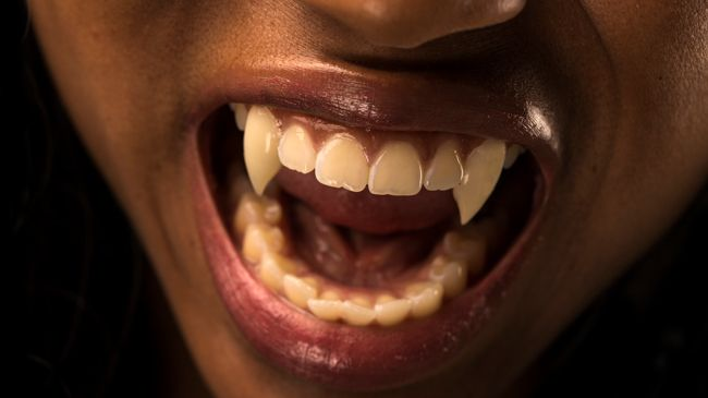 A black woman snarls to reveal a closeup of her vampire fangs!