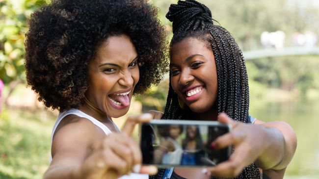 A woman with an afro sticks her tongue out as her friend in braids smiles demurely as they take a selfie together.