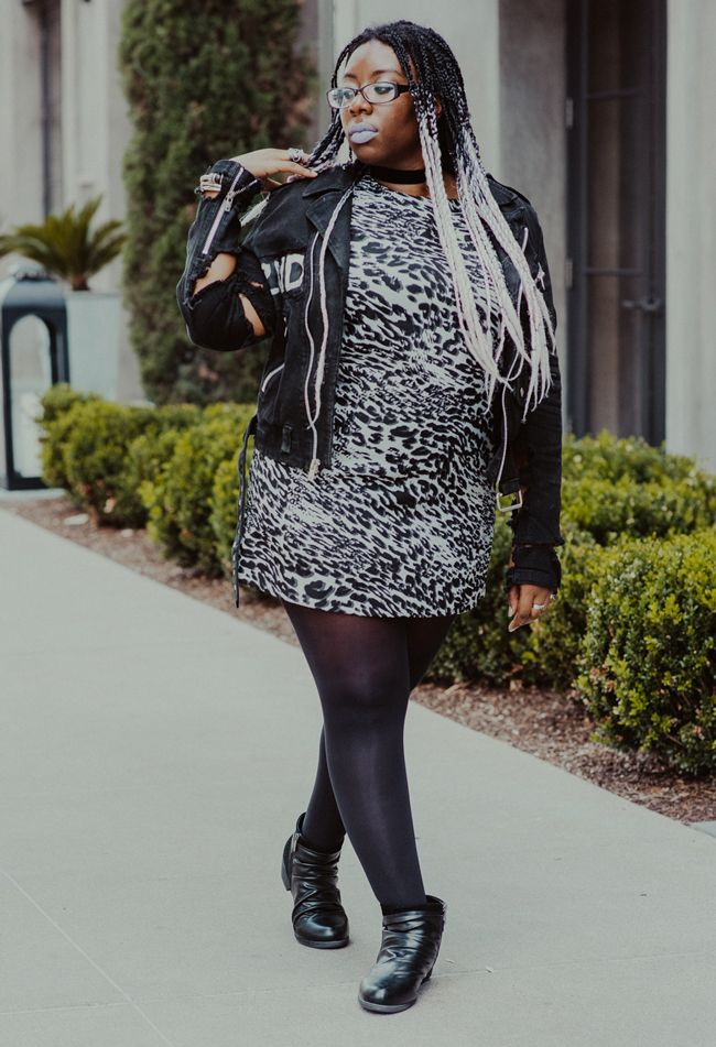 Editor April B walks along a sidewalk wearing a short gray leopard print dress, black tights, ankle boots, and a destroyed black jacket