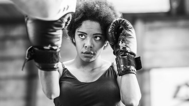 A woman with an Afro trains in boxing with both gloves up and reay