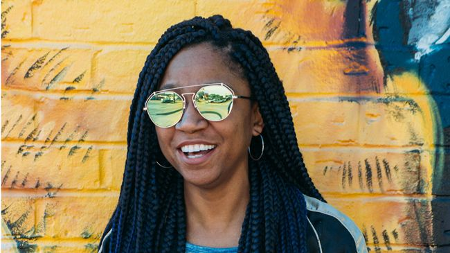 Gerilyn flashes a smile against a bright yellow brick background that constrasts with her indigo braids