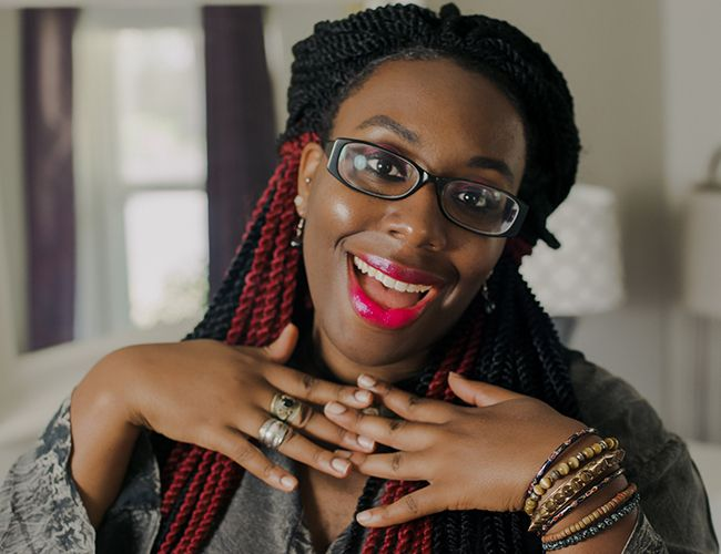 Woman wearing glasses smiling with pink lipstick and braids