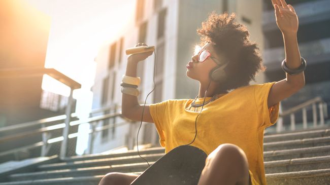A woman with an afro pumps her hands to her mp3 player, a skateboard between her knees