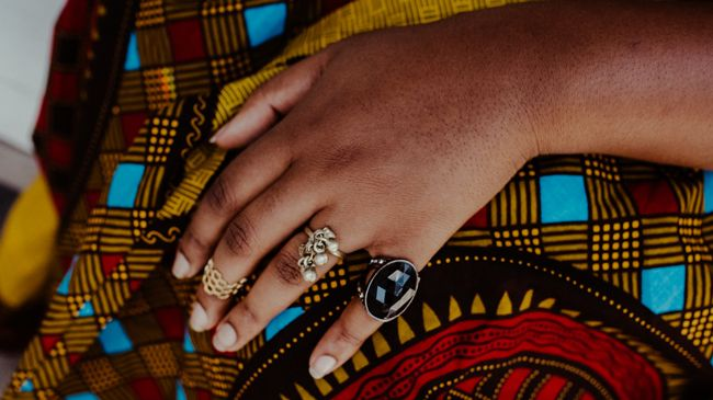 A close up of the Ankara patterns of the dress, and honeycomb, black jet, and bell adorned statement rings