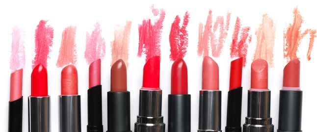 Eleven different shades of soft pink lipstick are stood next to a smear of their respective shades on a white background