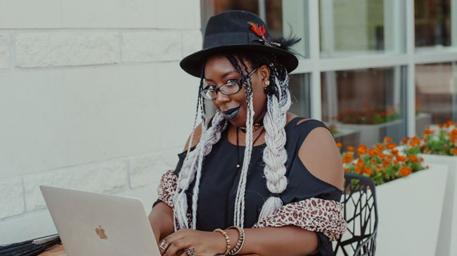 Editor April B types away at her laptop while flashing a black-lipstick covered smile to the camera