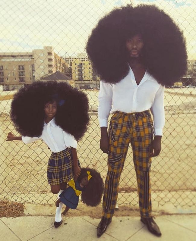 Father and daughter dressed alike with afros
