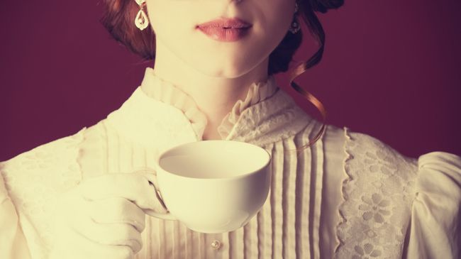 A woman with red curls in a starched white Victorian dress holding a cup of tea
