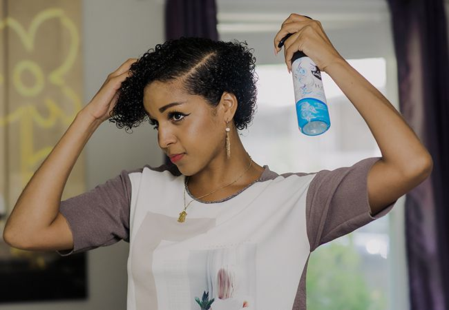 African-American woman spraying water on her hair