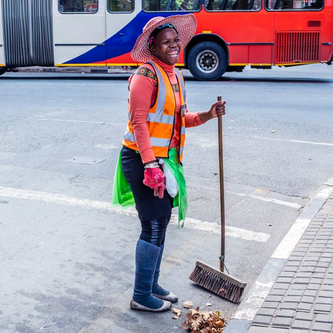 A smiling South African woman sweeps some leaves from the street