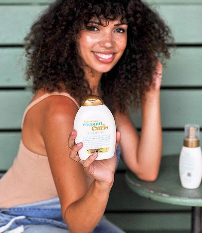 Woman smiling holding a bottle of shampoo