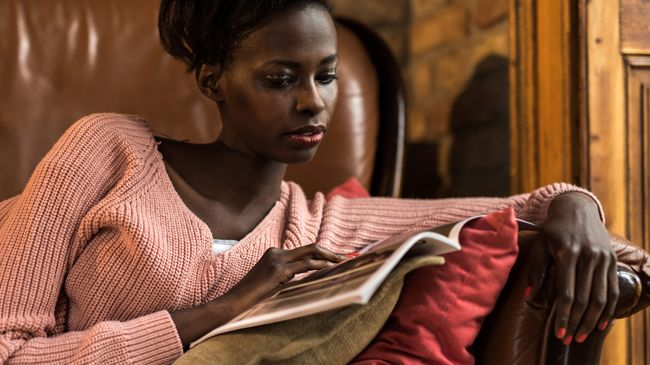 A black woman in a comfy sweater reads a magazine as she lounges on the couch