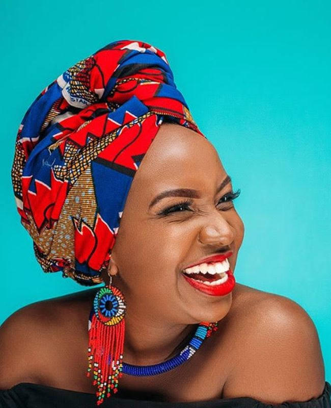 African-American woman smiling and wearing a headwrap