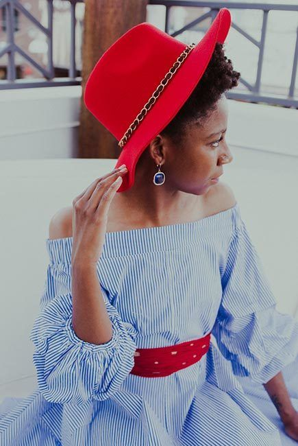 African-American woman, is dressed blue and white striped dress wears red wide-brimmed hat and black boots.