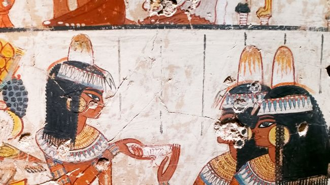 An ancient Egyptian wall painting depicting several dark skinned women with curly hair and traditional perfumed fat cones on their heads