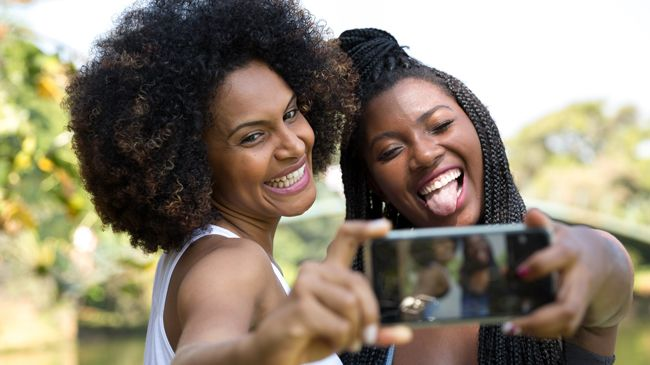 The same afroed and braided women take another selfie, but now their expressions have switched!