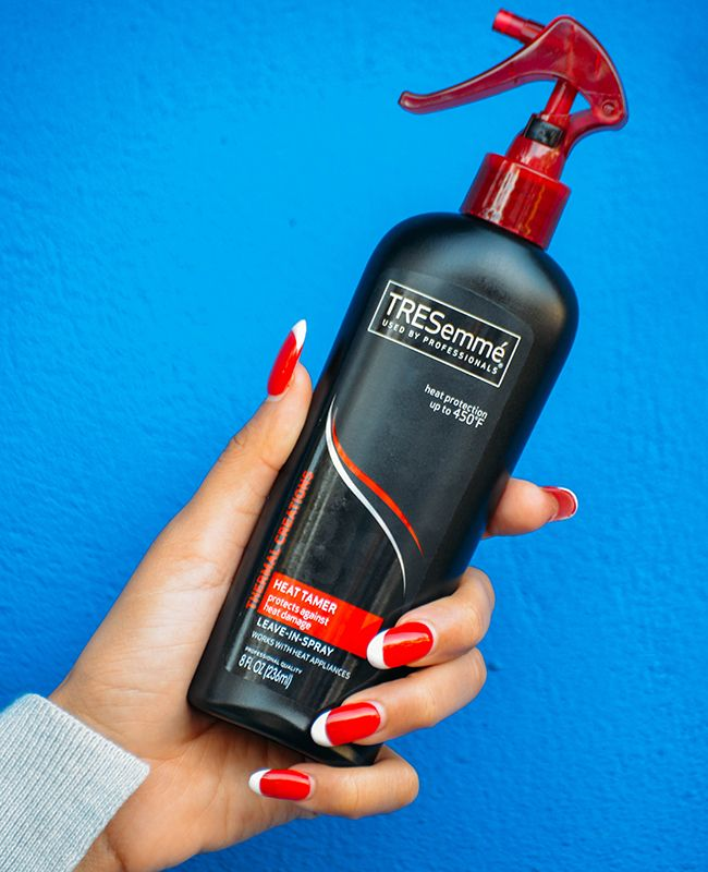 hand holding bottle of tresemme heat tamer spray
