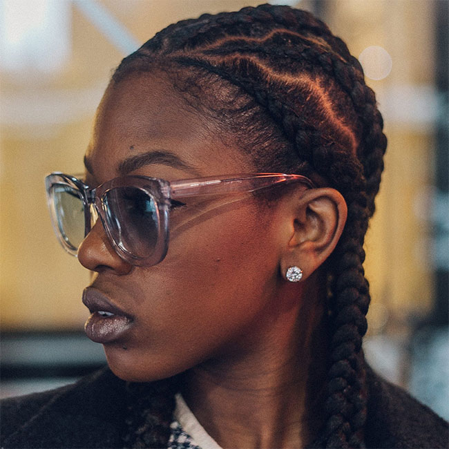 black woman with braided natural hair and zig zag parts wearing diamond earrings and sunglasses