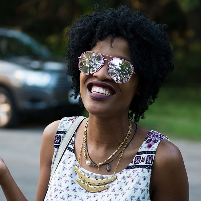 Beautiful dark skinned woman smiling bright on city street