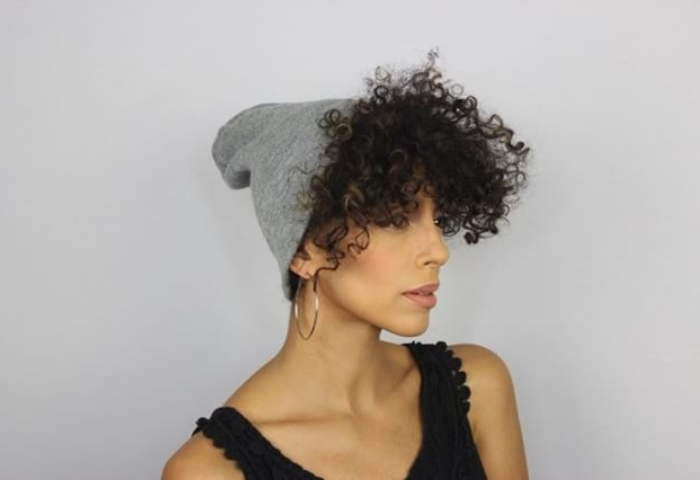 woman with natural curly hair wearing grey beanie and hoop earrings