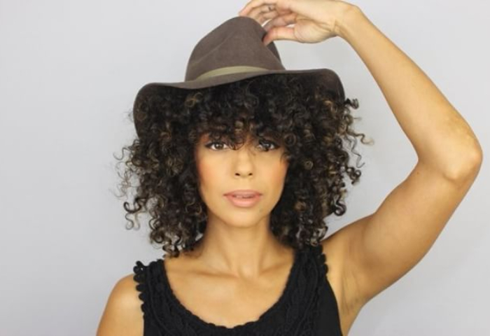 woman with natural curly hair wearing brown wide brimmed hat